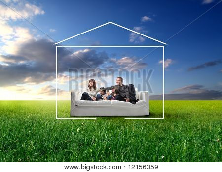 happy family seated on a couch in a grass field and surrounded by home drawing