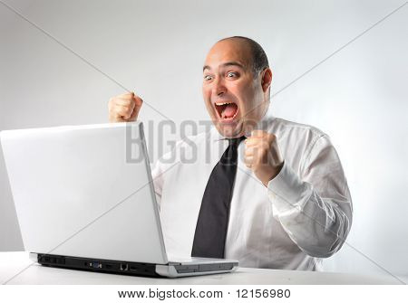 businessman exulting in front of the  laptop