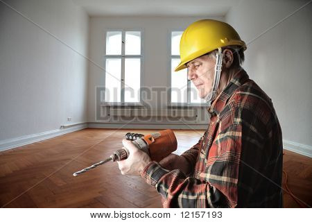 worker with drill in a house interior