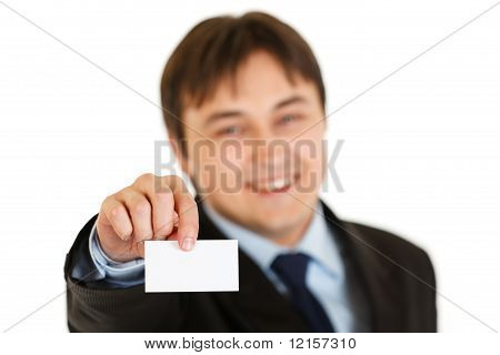 Smiling modern businessman holding blank business card isolated on white