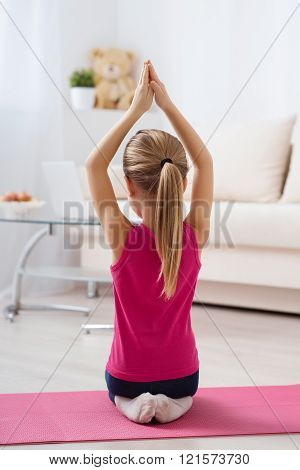 Girl is sitting with her back lifting hands up