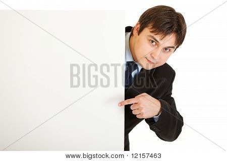 Smiling modern businessman pointing finger at blank billboard isolated on white