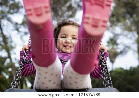 Happy three year old girl having fun on a swing. Selective focus