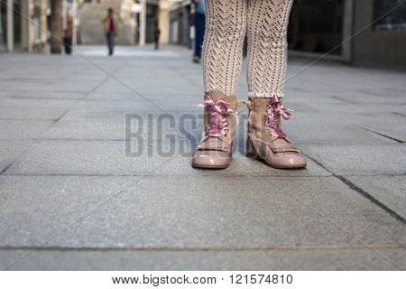 Happy three year old girl wearing pink satin lace boots on the city. Close up