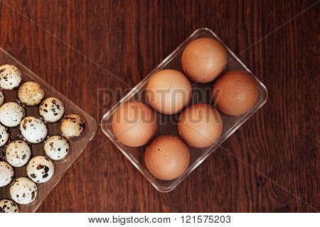 A goose egg hen egg and a quail egg on a wooden background.