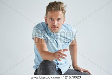 Brutal Man In A Shirt With Short Sleeves Sitting In The Chair , His Fists Clenched , Slightly Bent ,