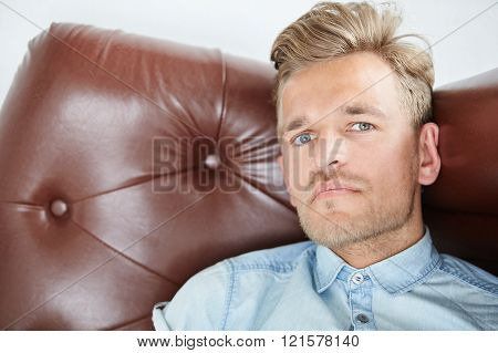 Brutal man in a shirt with short sleeves sitting in the brown chair looking in the camera close up p