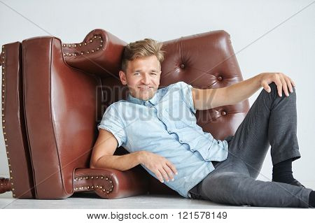Brutal man lying next to a brown leather armchair armchair lying on its side on the floor a man hold