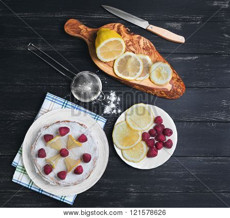 Lemon cake with raspberries a cutting board with slices of lemon sieve with icing sugar on a table of black color top view