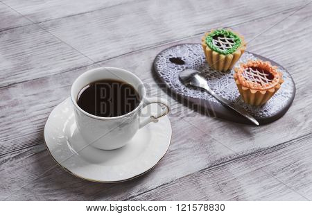 Small cakes petit fours tartlets with jam and cream ceramic board with a pattern of white lace with a cup of coffee espresso on a light wooden background