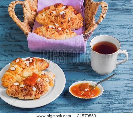 Breakfast Three croissant in a wicker basket on a purple cloth a croissant on a white porcelain plate sprinkled with almond petals apricot jam marmalade tea cup on a blue wooden background