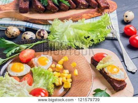 Lunch with croutons tapas parsley sprigs quail eggs in shell and fried eggs lettuce cherry tomatoes corn grains on dark wooden background