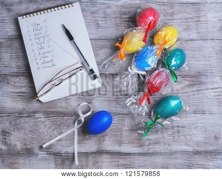 Congratulations on Easter on a light wooden table notebook with names pen colored eggs in transparent gift bag with satin ribbons gold-rimmed glasses top view