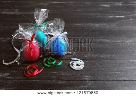 On a dark black background wooden table three chicken easter eggs in festive packaging with ribbons red blue green white red blue green white blank space for your text or congratulations