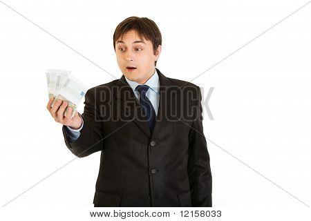 Surprised modern businessman holding money in his hand isolated on white