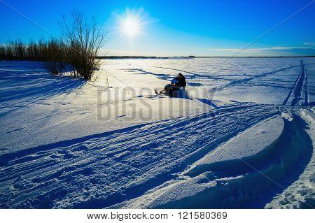 Snowmobile flies through a snowy field on a Sunny day .