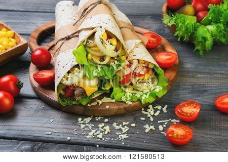 Sandwiches twisted roll Tortilla burritos three pieces on a wooden cutting board on a gray background lettuce cucumbers malosollnye cherry tomatoes corn onion rings meat
