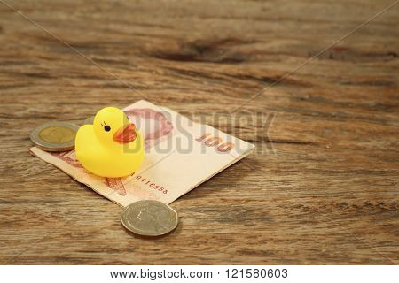 Yellow rubber duck with money of Thai Bath.