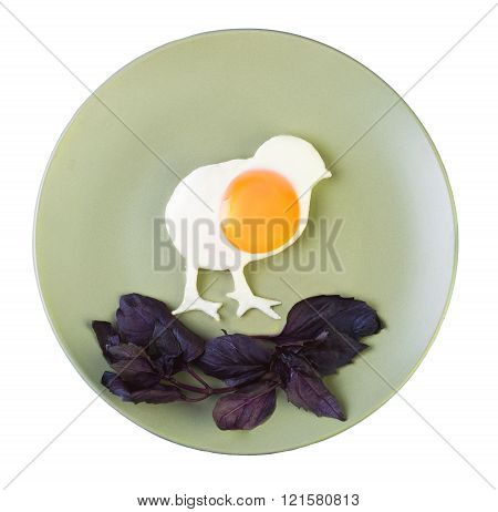 Scrambled eggs made in the form of chicken basil grass on the green ceramic plate isolated on white