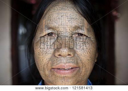KANPETLET, MYANMAR - DECEMBER 10, 2015: Photo of a Chin tribe tattooed faced woman (Daai tribe). Chin people, also known as the Kukis are a number of Tibeto-Burman tribal people.