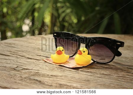 Yellow rubber duck , sunglasses with money of Thai Bath.