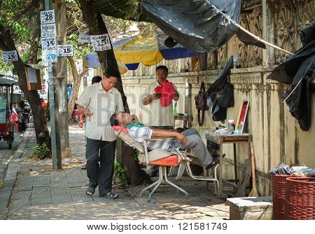 Barber Work At Open Air Shop On Pavement,