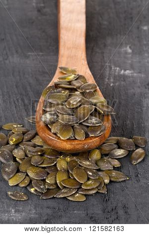 Unshelled pumpkin seeds in wooden spoon