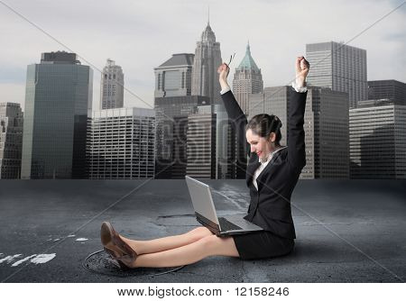 Woman exulting in front of a laptop in urban background