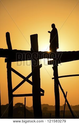 Monk on U Bein Bridge at sunset.