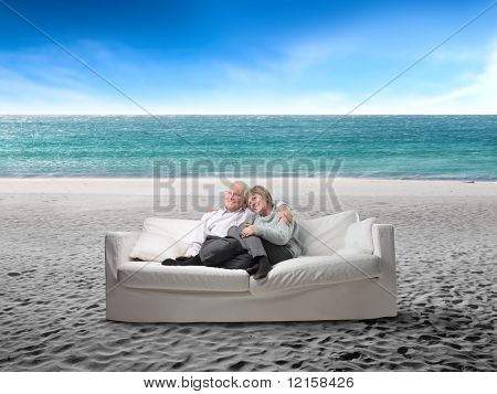 Portrait of a senior couple sitting in a sofa in the middle of a beach