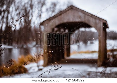 Snow Swirls in the Air Around a Covered Bridge. Shallow Depth of Field Focuses on Falling Snowflakes. Winter Nature River Landscape with Soft Focus Background and Copy Space.