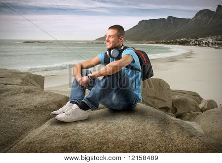Portrait of a young man with headphones and a rucksack sitting on a rock looking over a coastline