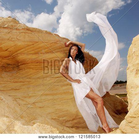 woman in white dress dancing on the desert
