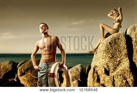 Young man carrying a lifesaver and beautiful woman sitting on a rock looking over the sea