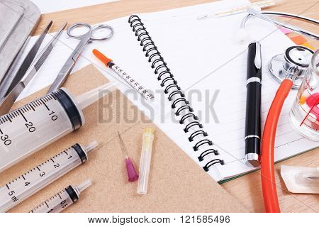 Stethoscope, syringes, scissors, pen and forceps on a white medical work surface.