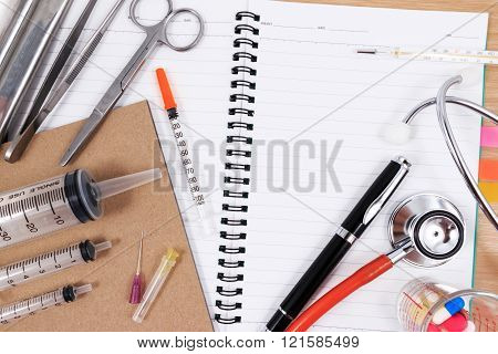 Stethoscope, syringes, scissors, pen and forceps on a white medical work surface. Photo taken from a
