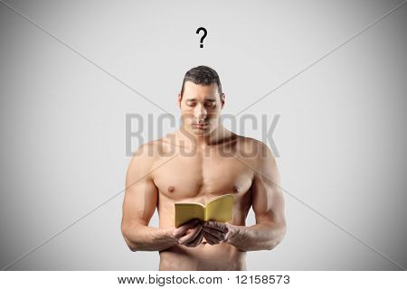 Portrait of a muscle man trying to understand what the tiny book in his hands says