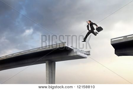 Portrait of a businessman leaping over the empty space between two parts of a broken highway bridge