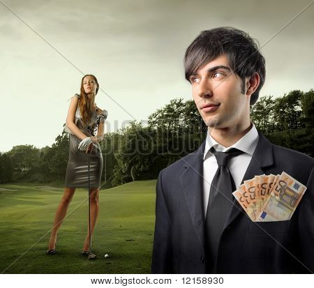 Portrait of a businessman with some banknotes in his breast pocket and an elegant woman holding a golf club