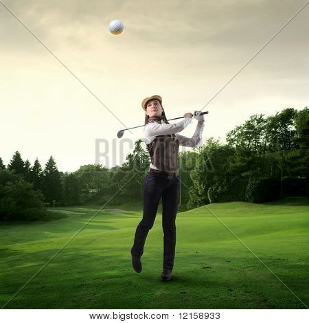 Portrait of a woman shooting a golf ball on a green meadow