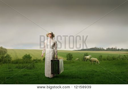 Portrait of an elegant woman carrying an old suitcase on a green meadow