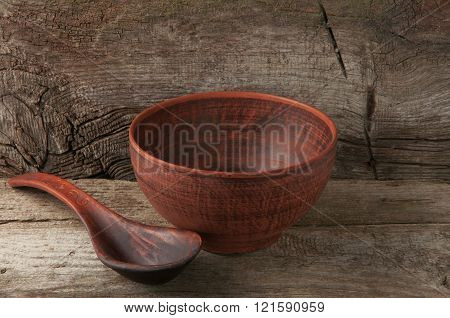 empty clay bowl with spoon on wooden background closeup. Fasting. Lent.