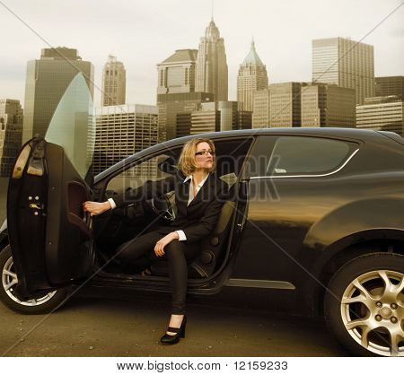 Portrait of a businesswoman coming out of a car