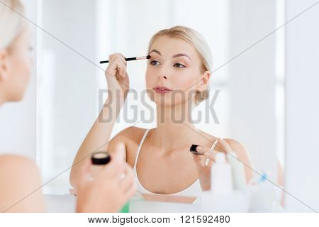 beauty, make up, cosmetics, morning and people concept - young woman applying eyeshade with makeup brush and looking to mirror at home bathroom