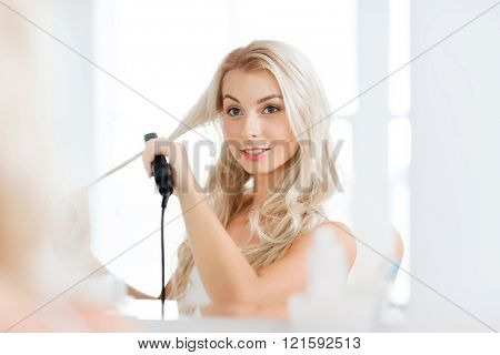 beauty, hairstyle, morning and people concept - smiling young woman with styling iron straightening her hair and looking to mirror at home bathroom