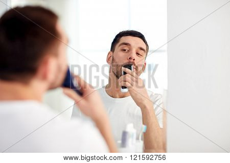beauty, hygiene, shaving, grooming and people concept - young man looking to mirror and shaving beard and mustache with trimmer or electric shaver at home bathroom