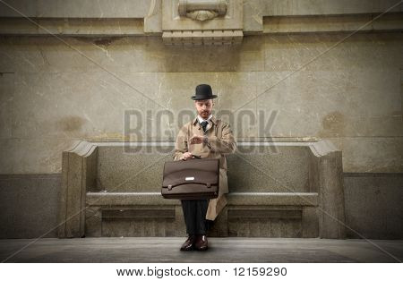 Portrait of a businessman sitting on a bench in a station and looking at his watch