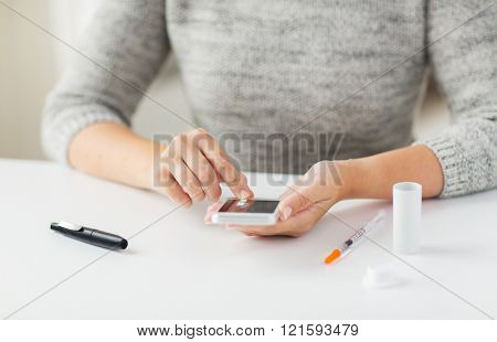 medicine, diabetes, glycemia, health care and people concept - close up of woman hands with smartphone checking blood sugar level by glucometer at home