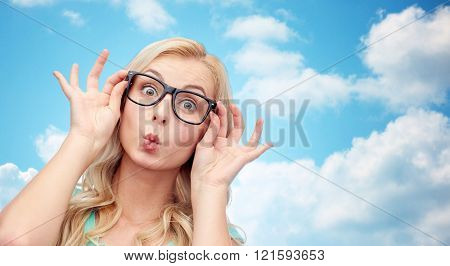 vision, education and people concept - happy young woman or teenage girl glasses making funny fish face over blue sky and clouds background