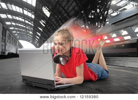 Young woman lying on the platform of a train station with a laptop in front of her